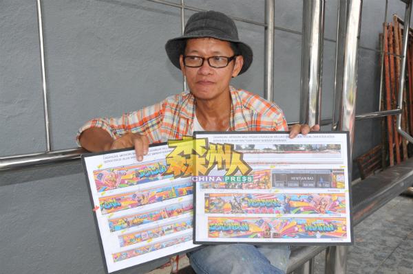 """赖昭光手持两个版本的""""森州发展史""""壁画构思图,当中一些构思图已经过修改。"""