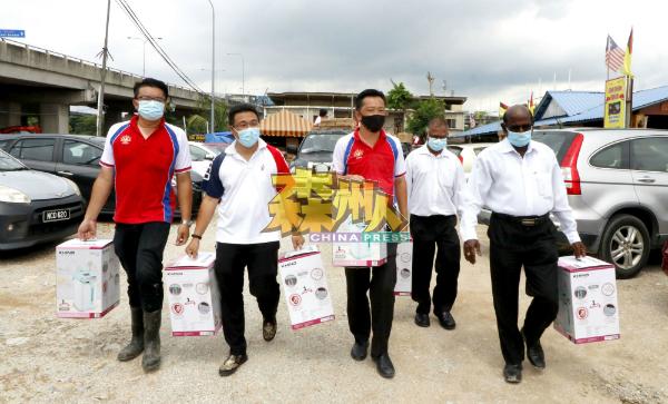 P古拿(前排右起)、谢琪清、李凯业及李汉强,提着电水煲准备派发给水灾灾民。