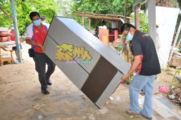 黄运灵(右)与庄雪和合力抬着刘天财捐出的衣橱进屋。