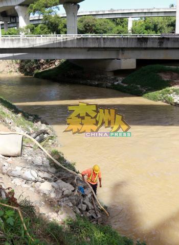 水利灌溉局员工走下河里,检查淤积河里的淤泥深度。