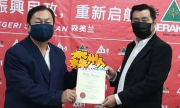 李汉坤(左)从协调官蔡同财手中接过委任状。