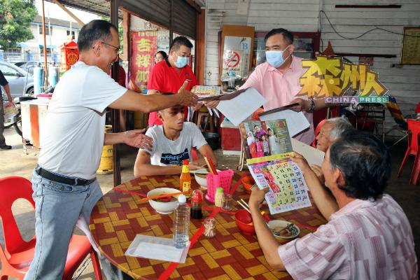 陆兆福(站者右起)与张洪铭派发月历给芭蕾新村村民。