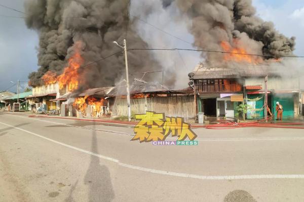 亚逸玛旺镇的8间木板店屋遭大火吞噬,滚滚浓烟冲天起,情势骇人。