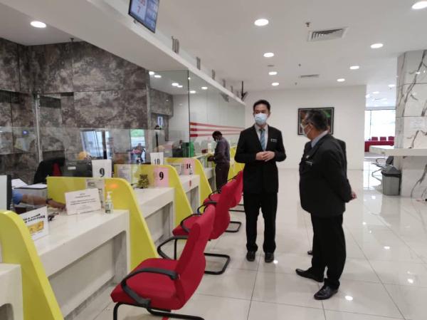 张聒翔(右2)与查扎里(右)巡视芙蓉市政局服务柜台的运作情况。