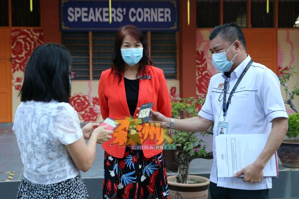 森教育局官员凯鲁(右)亲自巡视振中总校应考生首日开课的实况,中为欧阳满妹。