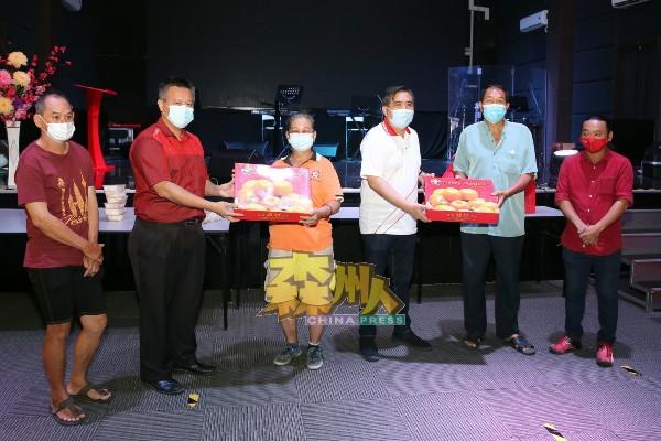 无需再担心被逼迁的武吉中居民代表沉亿善(右2)及萧玉莲(左3),分别赠送一盒芦柑感谢陆兆福(右3)及吴金财(左2)。