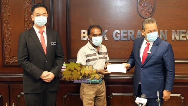阿米努丁(右)移交医疗器材援助金予受惠女生茜玛拉达的父亲拉古(中),旁为张聒翔。