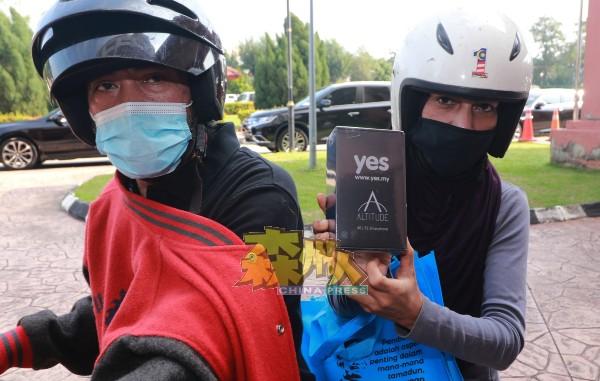 B40家庭受惠者展示他们所得到的手机。