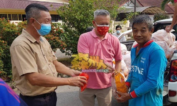 林国坚(左起)和赖振光颁赠新年恩物给汝来村民。
