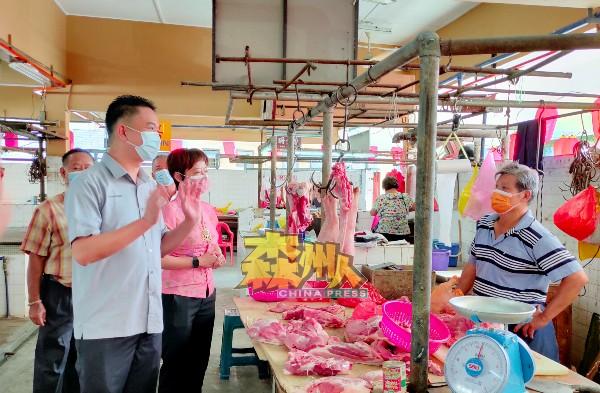 张聒翔(左)通知每个巴刹摊贩,巴刹营业时间获准延长至下午5时,左2是陈丽群。