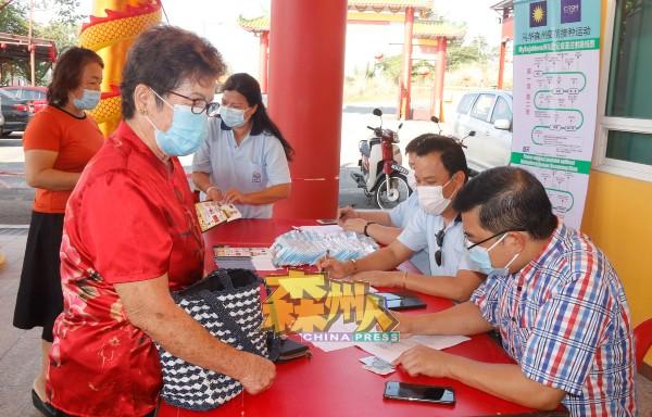 工作人员为没有智能手机的乐龄人士填写表格,以登记接种疫苗。