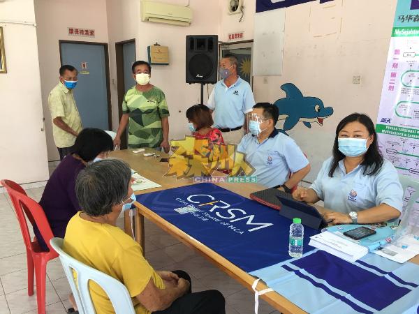 何彩思(坐者右起)、吴健南、温雅兰在协助万茂新村的村民登记注射疫苗。站者右起林国坚、邓家福及温启文。
