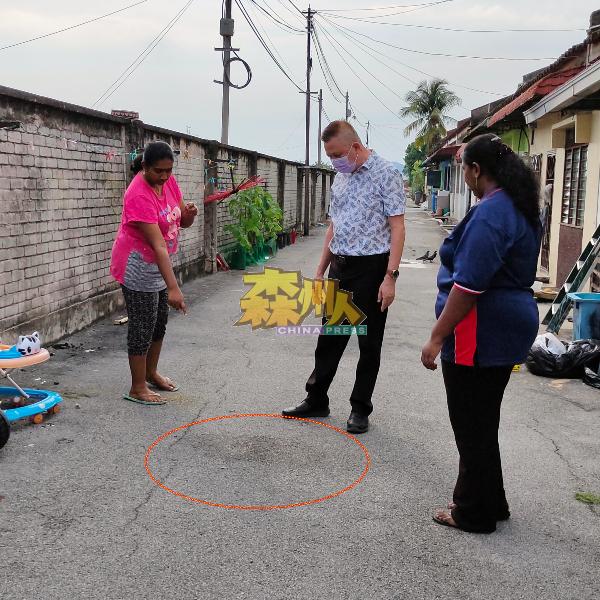 安美嘉(左)向叶耀荣(中)指出女婴被发现的地点,垃圾已清,路面尚留着包裹女婴塑料袋的血水痕迹。