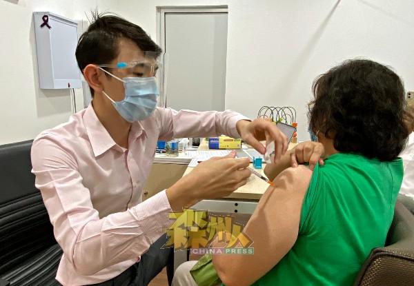 吴铭利(左)为民众进行疫苗注射。