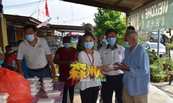 陈璇玮(前排左)派发早餐予榕吉新村村民享用。潘宥磬为中者。