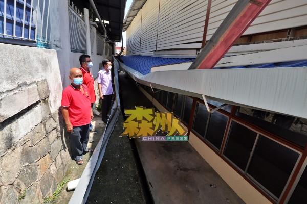 刘天财(左起)、李汉强、谢琪清视察在星期一风灾中被刮落的亚沙新村民众会堂排水槽。