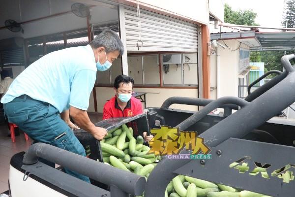 李恒华(左)亲自把黄瓜载返拉务八里新村,以派送给村民。