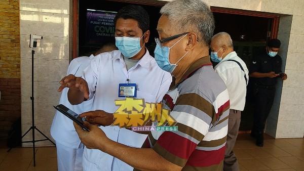 梁亚海(右)面对My Sejahtera手机应用程式问题,获医务人员亲切细心说明,最后获得解决。