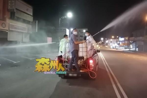 数名消毒志工站在四驱车后部,为所到之处喷洒消毒液。
