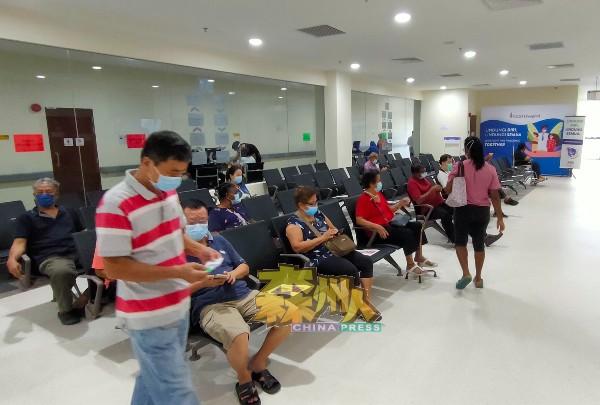 公众在室内等候室等待接种疫苗。