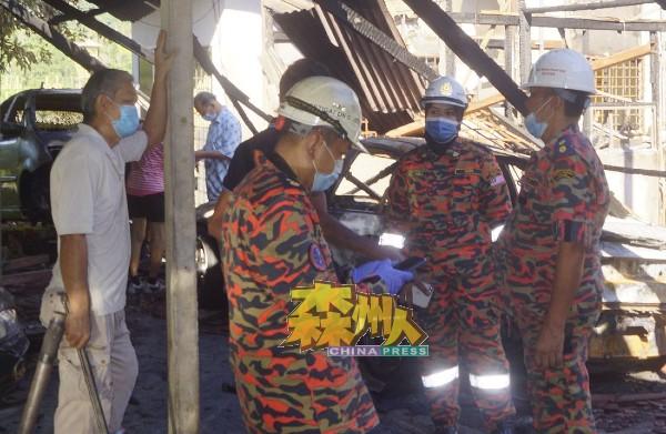 消拯局鉴证组人员向陈国鸿(左)了解火患详情,并进行取证调查火患原因。