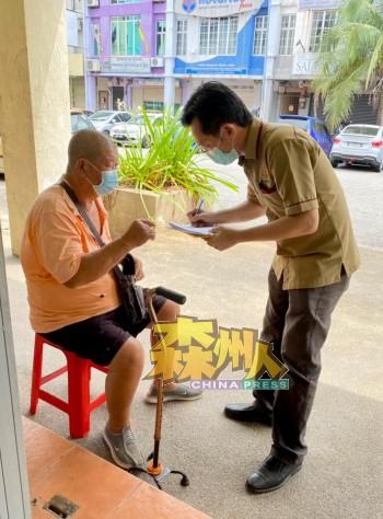 谢琪清(右)亲自为上门的民众登记接种疫苗。