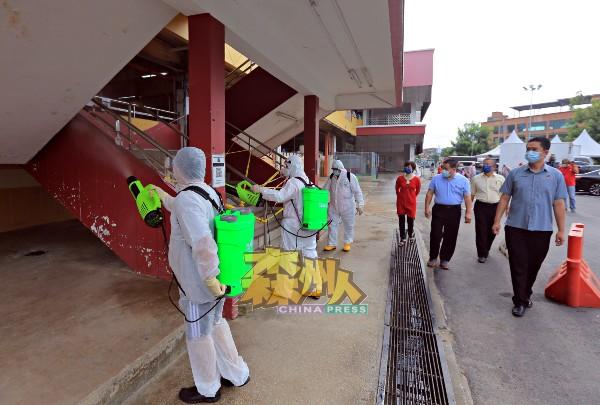 张聒翔(前右起)、许礼叠、周世扬及陈丽群巡视消毒队进行消毒。
