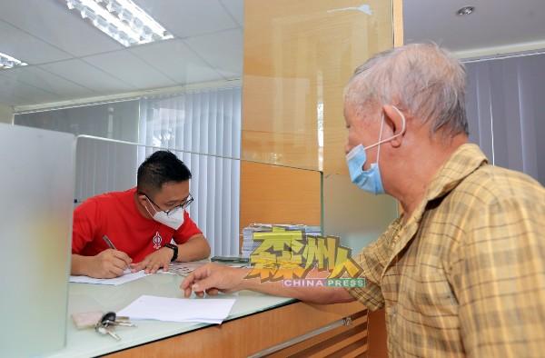 何永铧(左)在移交贩商的筛检报告的同时,也查证贩商的个人资料。