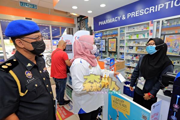 药剂行工作人员向艾茵(右2)展示所售卖的自助冠病测试剂盒价格。