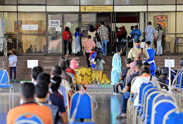 大批民众周一早上在接种中心外有秩序的排队,且遵守SOP,等待进入接种中心接种疫苗。